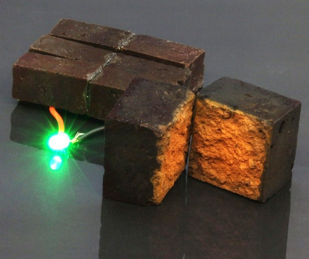 El dispositivo de ladrillo rojo desarrollado por químicos de la Universidad de Washington en St. Louis enciende un diodo emisor de luz verde (laboratorio D'Arcy: Universidad de Washington en St. Louis)